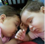 Sleeping twins with honey colored skin, brown hair, and full chubby cheeks.