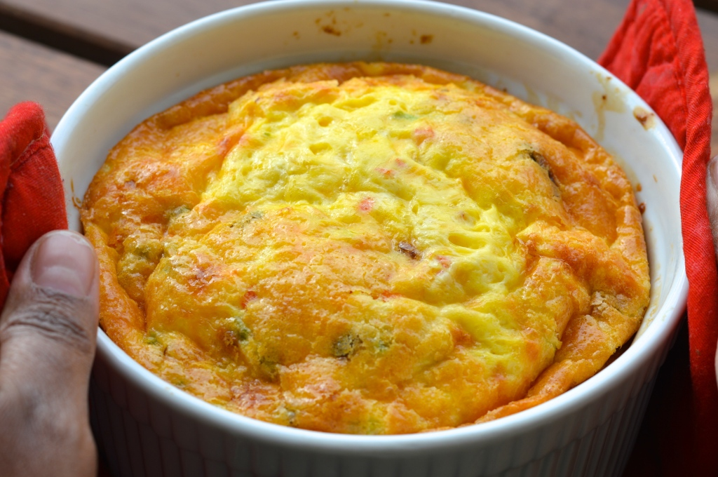 Image shows a fresh from the oven fritatta in a large white ramekin held on the sides with red potholders and a brown skin hand