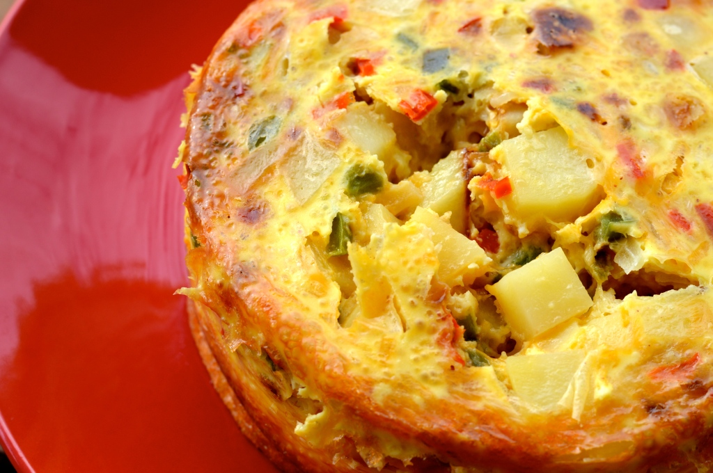 Image of a fritatta with the potatoes, flecks of red pepper, green peppers, and onions
