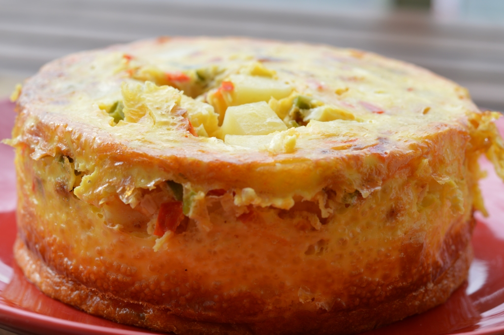 Image of a cooked Fritatta taken from the side showing three inch tall fritatta with flecks of red bell pepper and potato