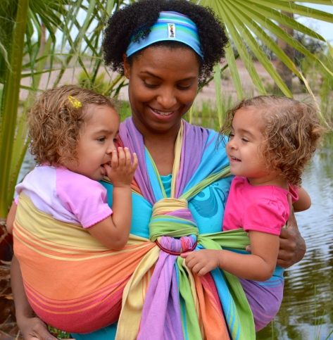 Image of a brown skin woman wearing twin toddlers, one on each hip, in a rainbow colored woven wrap with two rings at the chest