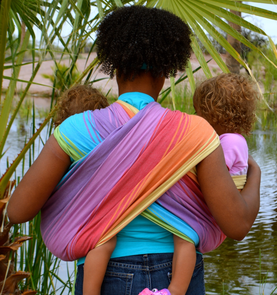 The back view of the tandem hip carry showing the rainbow wrap crossing in an X pattern across the brown skin woman's back. Babies are worn in the wrap one on each hip