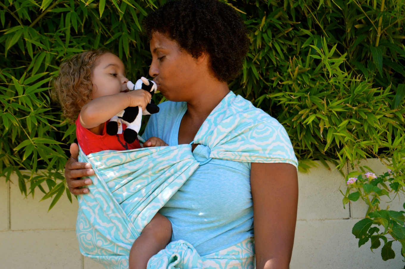 Natural haired African American Momma with her curly haired blond twin toddler in a teal green woven wrap with scalloped seashells and pearls in a Reinforced Robin's Hip Carry with a Ring. The Momma has her hand gently around baby's back and is kissing a stuffed animal cow baby is offering to Momma.