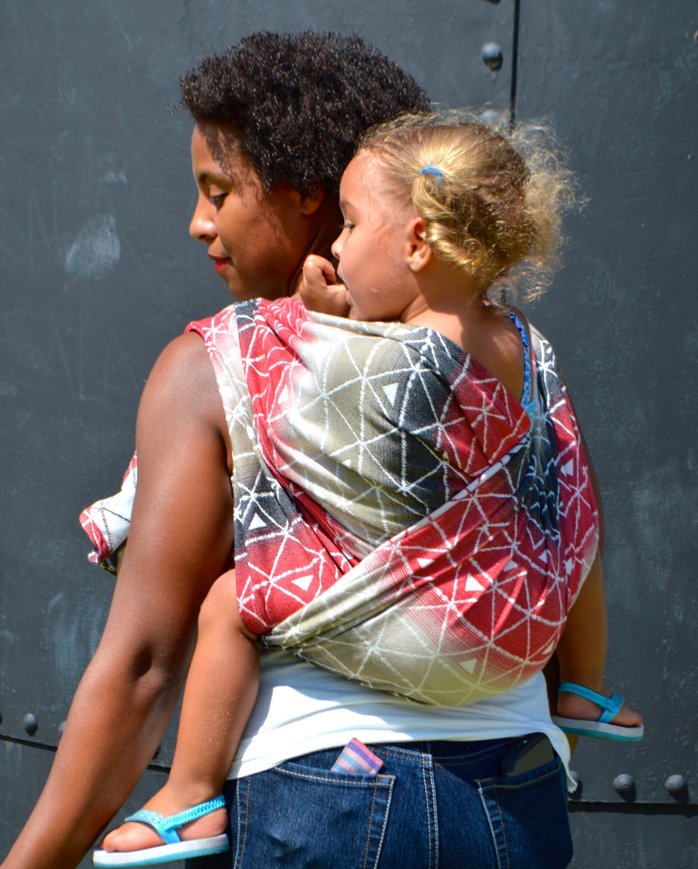 Medium brown African American Momma with dark natural curly hair wears her light brown skinned, blond haired baby with pony tails in gradient colored wrap red, black, light brown, and white with delta triangles positioned between lines of delta triangles.