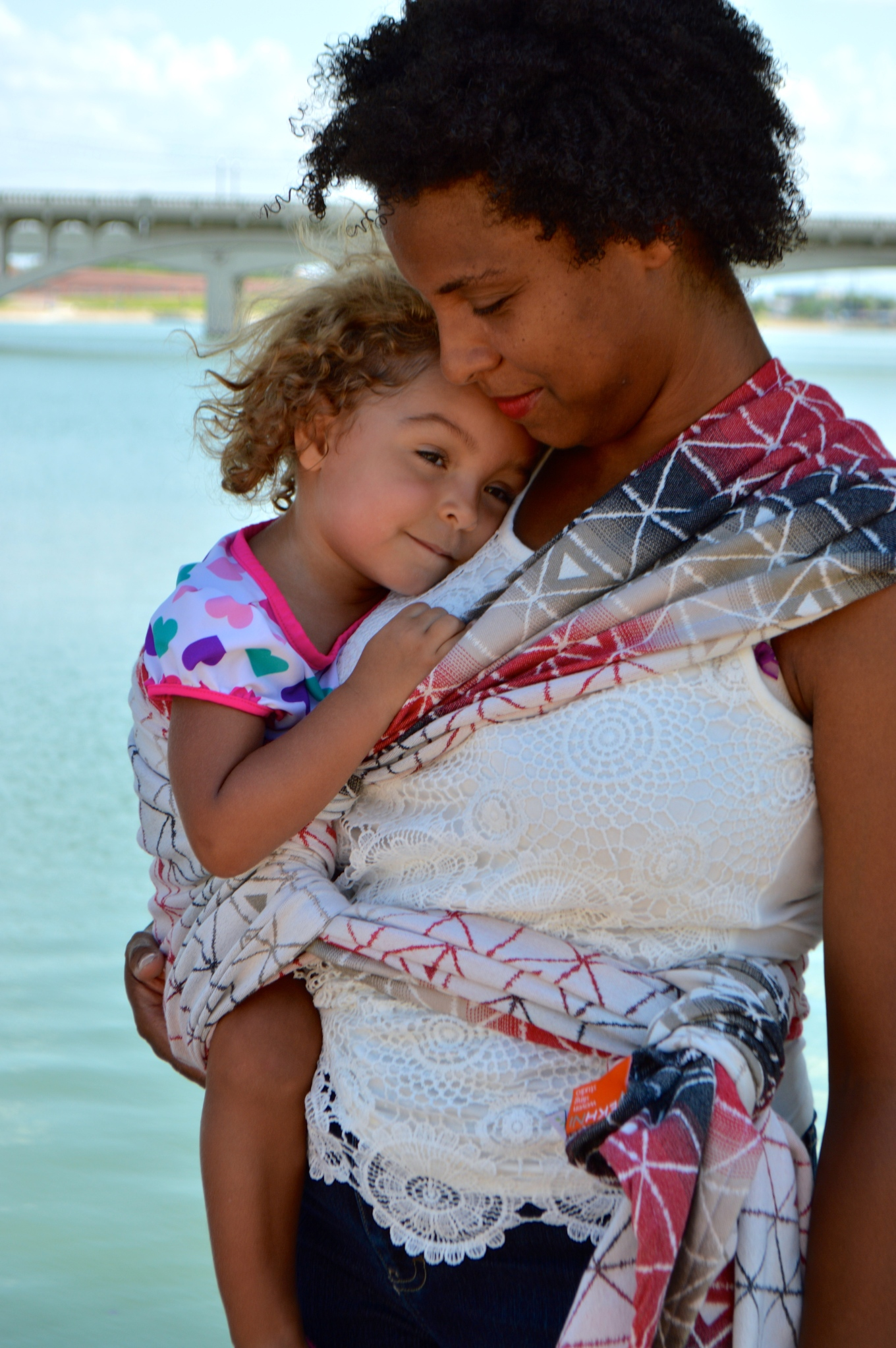 Natural curly haired African-American Momma n white lace blouse shares a snuggle with her curly haired blond toddler of light brown skin. Baby wears a swim shirt with pink, purple, and teal hearts against a white background. The lake and a bridge are in the background.