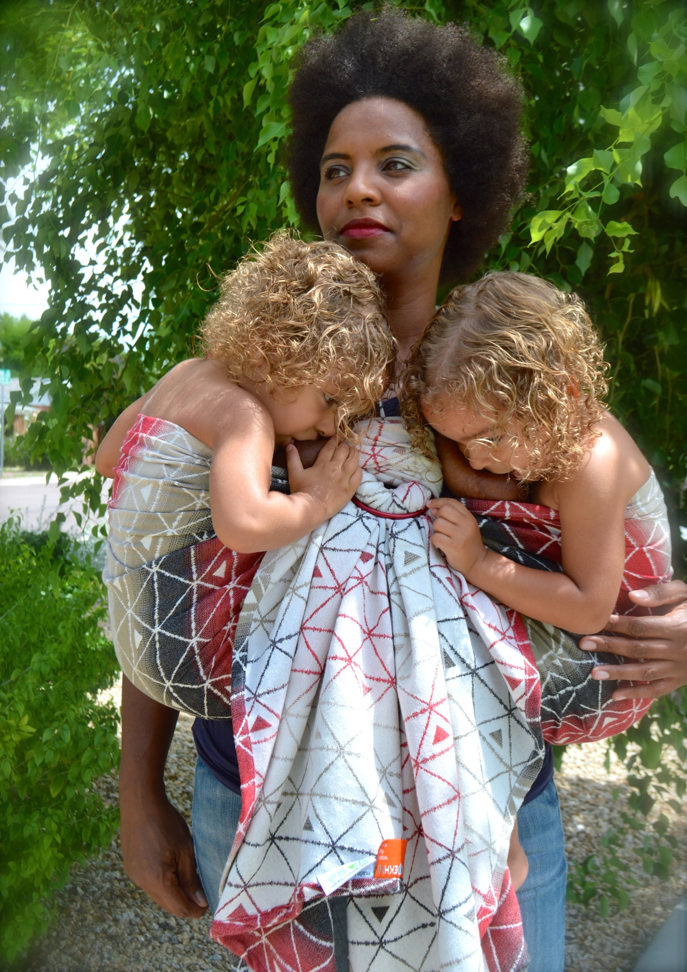 Proud African American Momma stands tall with tall natural afro and red lipstick. Twin toddlers are shirtless, blond curls free, nursing in tandem hip carry. The wrap is gradient colors of red, black, brown, and white against a dominant white reverse side. The large sling rings are red.