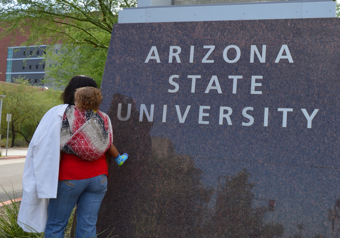 African American Mother wearing her Blond haired, light brown baby in Symmetrical Half Jordan's Back Carry. Momma and Baby stand in front of Arizona State University Sign, the laboratory in the distance. Momma has white labcoat over her left shoulder.