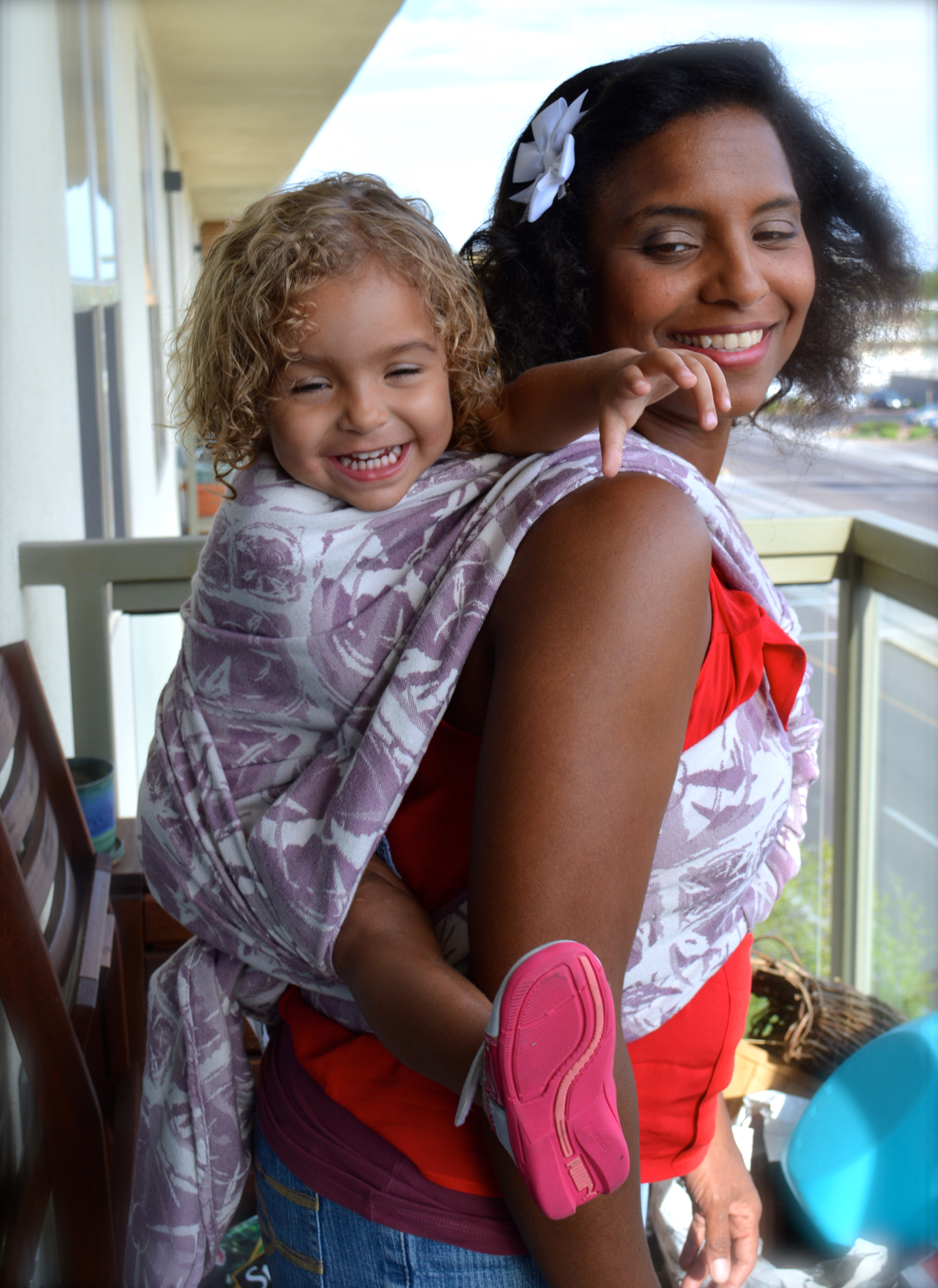 Medium Brown Momma with big natural hair in a red shirt wears her blond haired baby on her back in a white and purple wrap. The carry is a one shouldered carry with the wrap passed back over to show the other side .