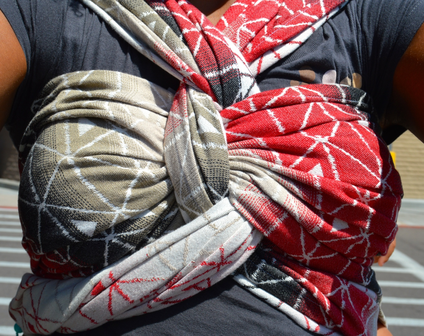 Closeup view of fabulous finish of back carry. The wrap is twisted above a lose chest pass. One tail is threaded under the wrap, the other over before twisting again below the chest pass. The wrap gradients color from red to black to brown then white.