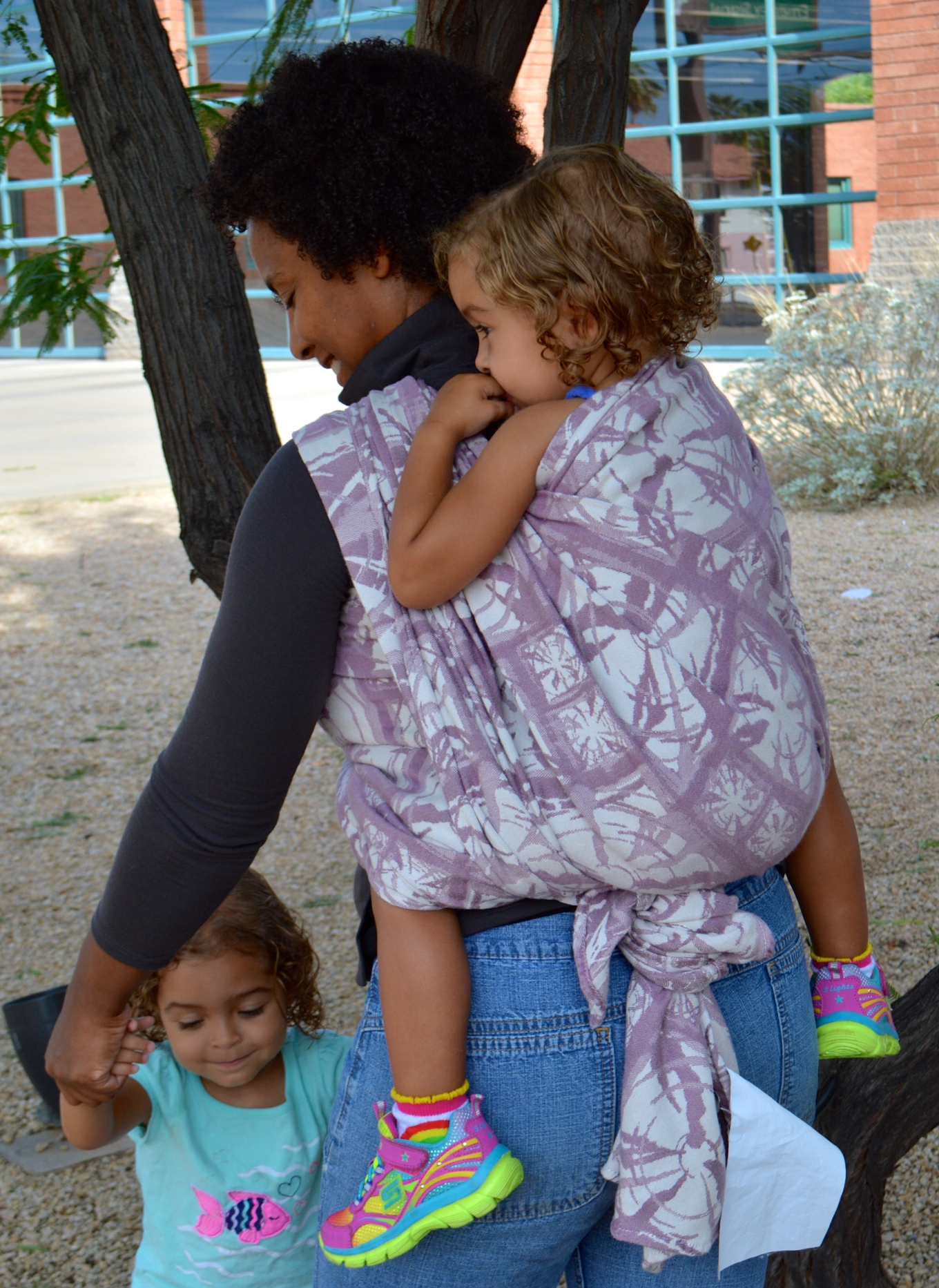 Medium Brown momma with Natural hair wears blond baby in neon colored shoes in pale purple and white wrap on her back. She is hands free to hold her other baby's hands and dance outside the fire station.