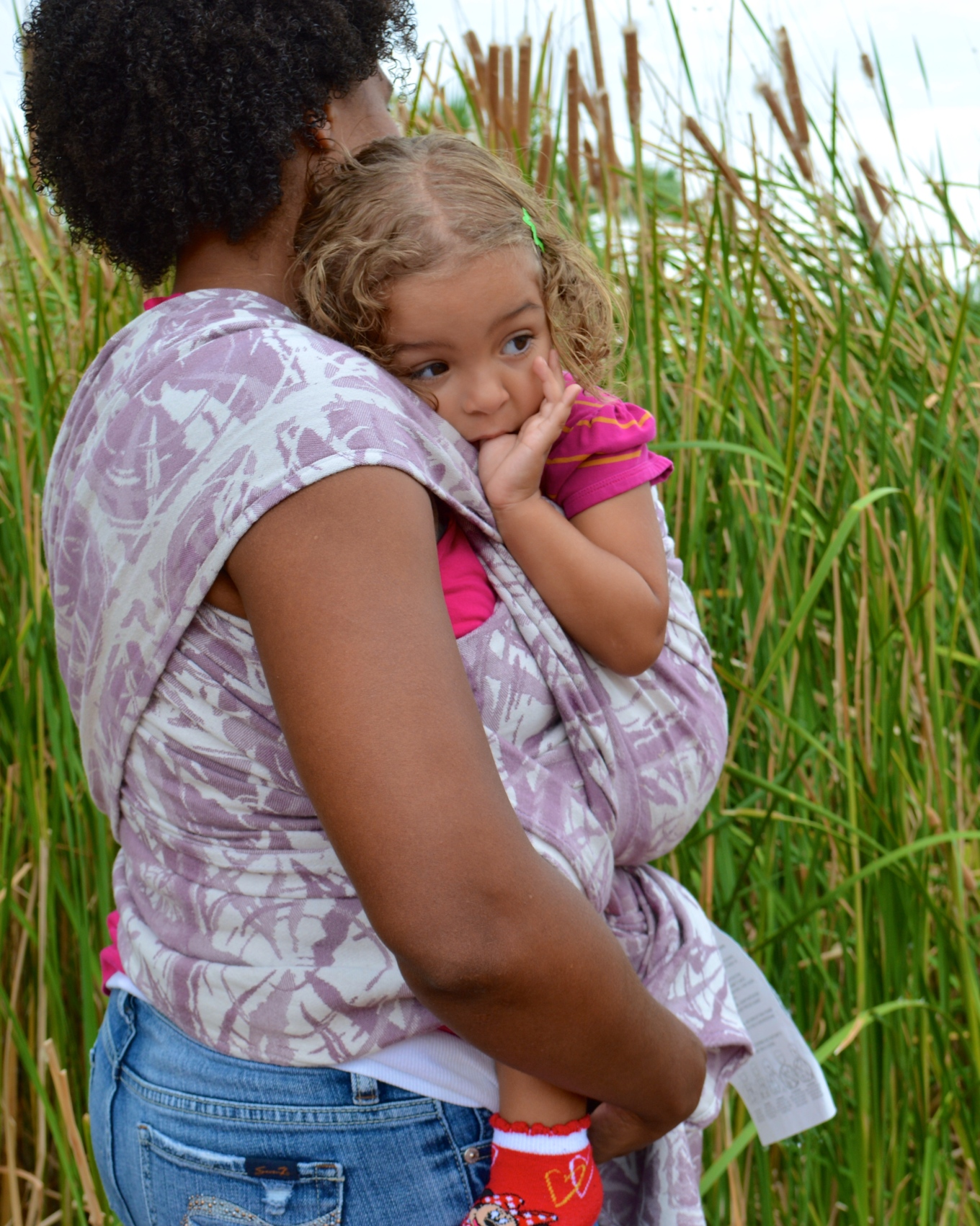 Medium brown natural haired Momma wears her baby in a pink striped shirt in white and pale purple wrap in front of the cattail bushes near the lake