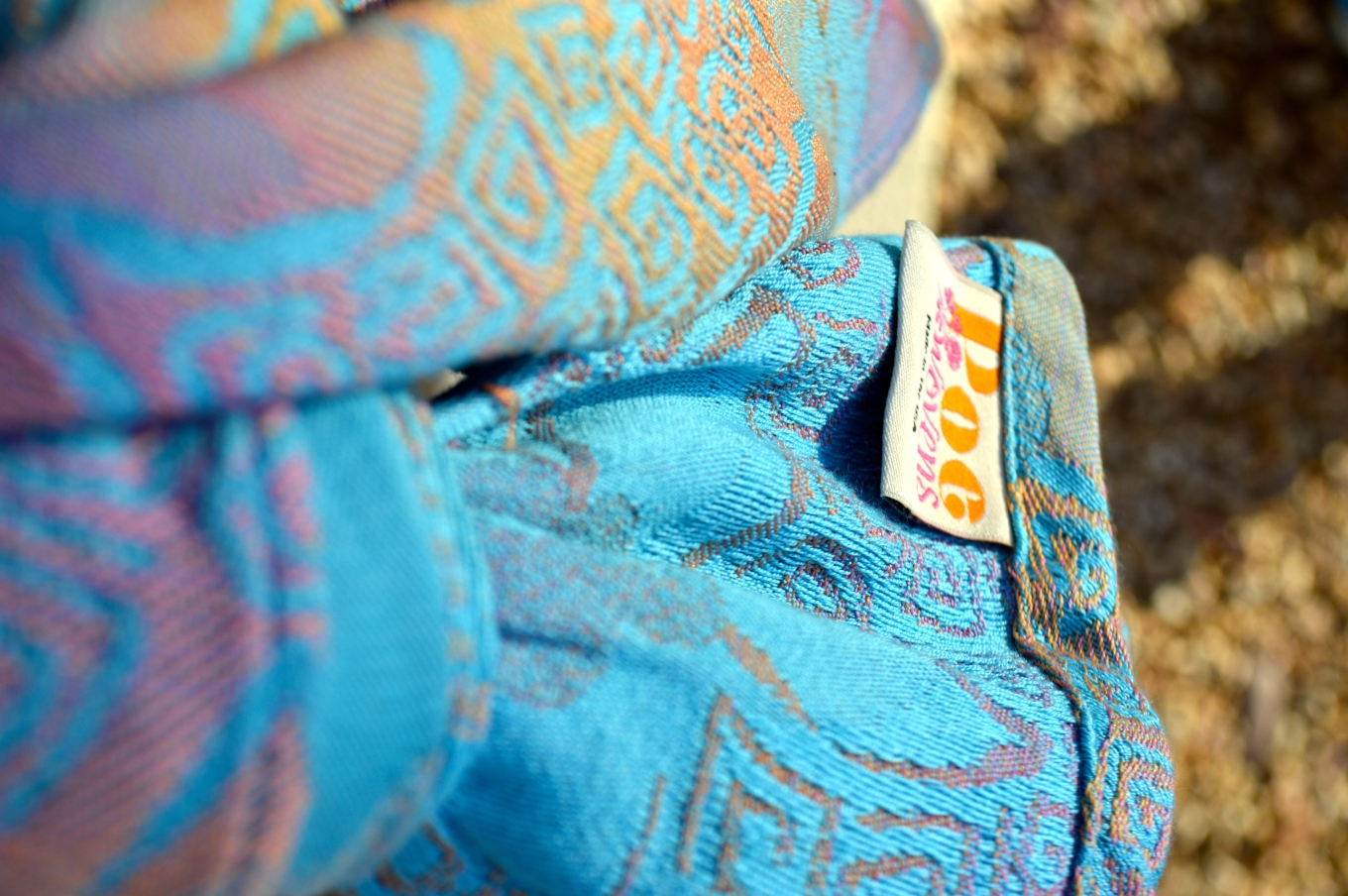 Image shows the view looking down from the wearer's point of view of the knot tied to secure the carry. The company label is visible in the foreground and the rocks below are fuzzy in the background. Close up view of gradient color orange to pink Jonquil flowers against a pale blue background. The flowers and geometric circle tendrils are raised from the fabric of the wrap adding texture.