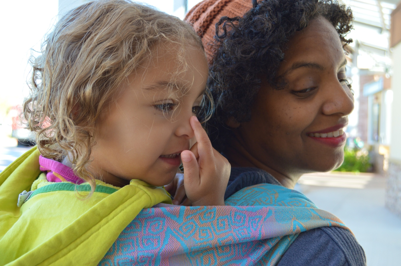 Medium brown Momma with natural curly hair wears orange-brown knit cap and red lipstick. Her light brown, curly blond haired toddler wears a neon yellow hoodie and is pointing to her nose. Baby is on Momma's back in a Double Hammock carry in a gradient orange to pink on pale blue background woven wrap with embossed jonquil flowers.