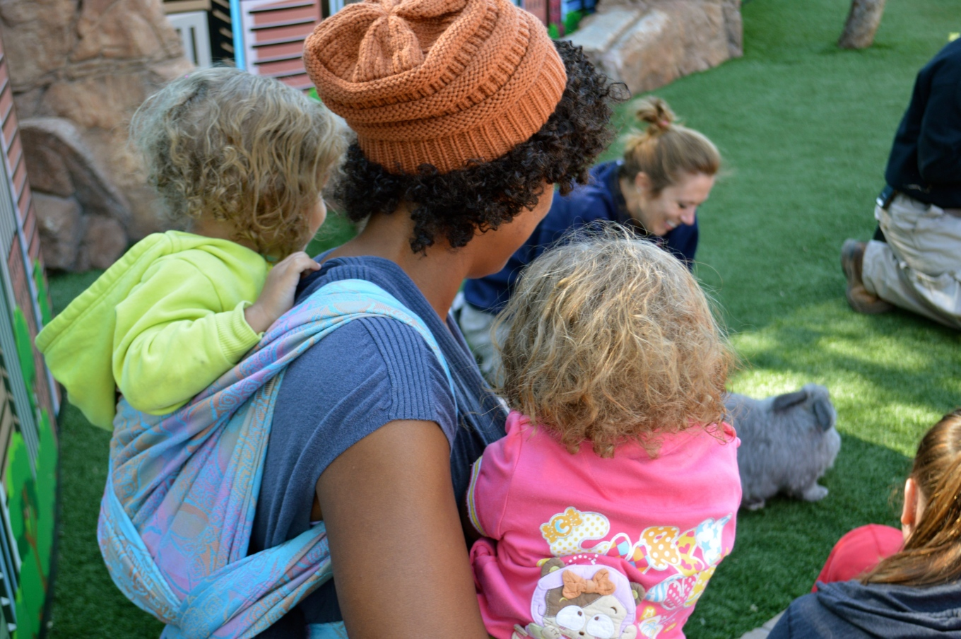 Momma and two toddlers observe grey giant Flemish rabbit and other animals not in view. Rabbit is in zookeeper's hands, hopping on green artificial turf grass. Momma wears one toddler and other light brown, blond haired toddler wears a pink sweater with a monkey sits in Momma's lap. Medium brown Momma with natural curly hair wears orange-brown knit cap and red lipstick. Her light brown, curly blond haired toddler wears a neon yellow hoodie. Baby is on Momma's back in a Double Hammock carry in a gradient orange to pink on pale blue background woven wrap with embossed jonquil flowers.