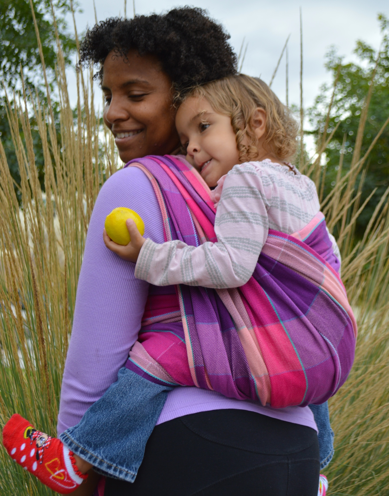 Image of medium brown momma with natural curly hair smiling at her baby as she wears light brown curly blonde haired toddler in a tonal magenta, pink, purple wrap with turquoise pinstriping.