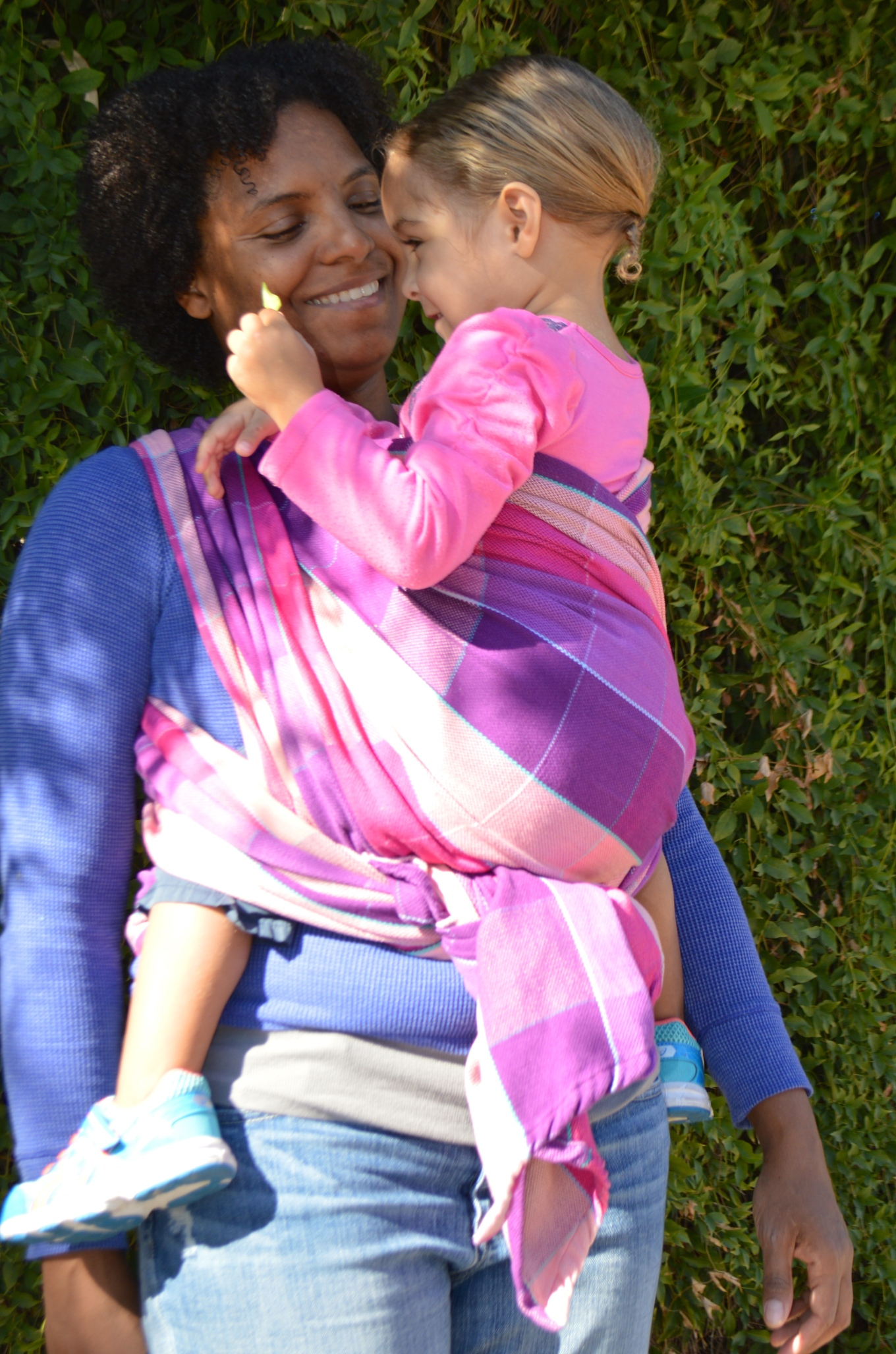 Image of medium brown momma with natural curly hair smiling at her baby as she wears light brown curly blonde haired toddler in a tonal magenta, pink, purple wrap with turquoise pinstriping. Baby is wearing a pink shirt and looks at the leaves in her hand.