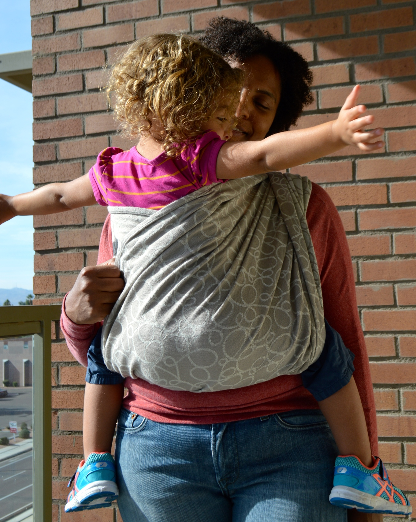 Medium Brown Momma wears light brown blond haired toddler with arms outstretched for a hug in a dark tan colored wrap with light tan colored swirls. The wrap crosses behind baby's back just under her arms.