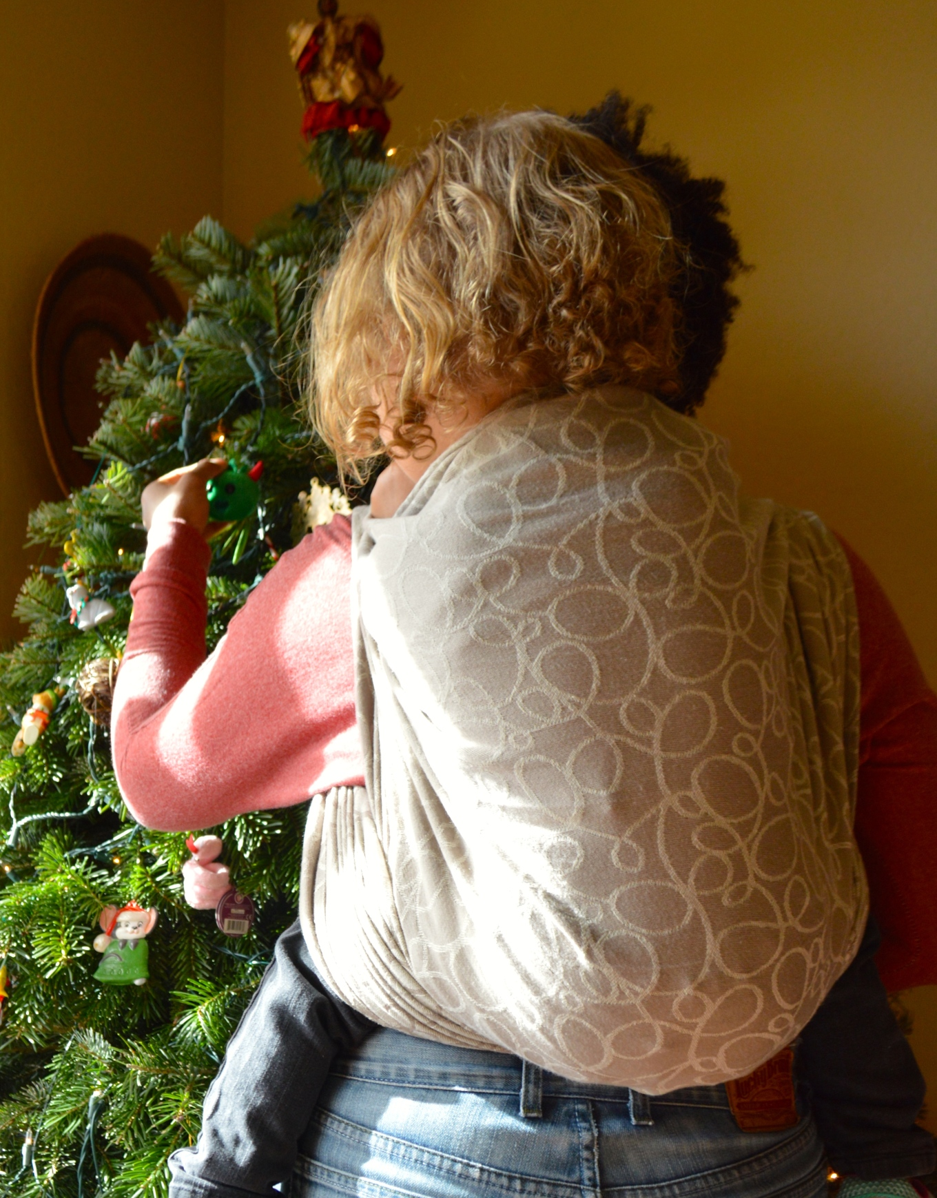 Blonde curly haired toddler is worn on back of medium brown momma in a dark tan wrap with light tan swirls. They are hanging ornaments on the Christmas Tree