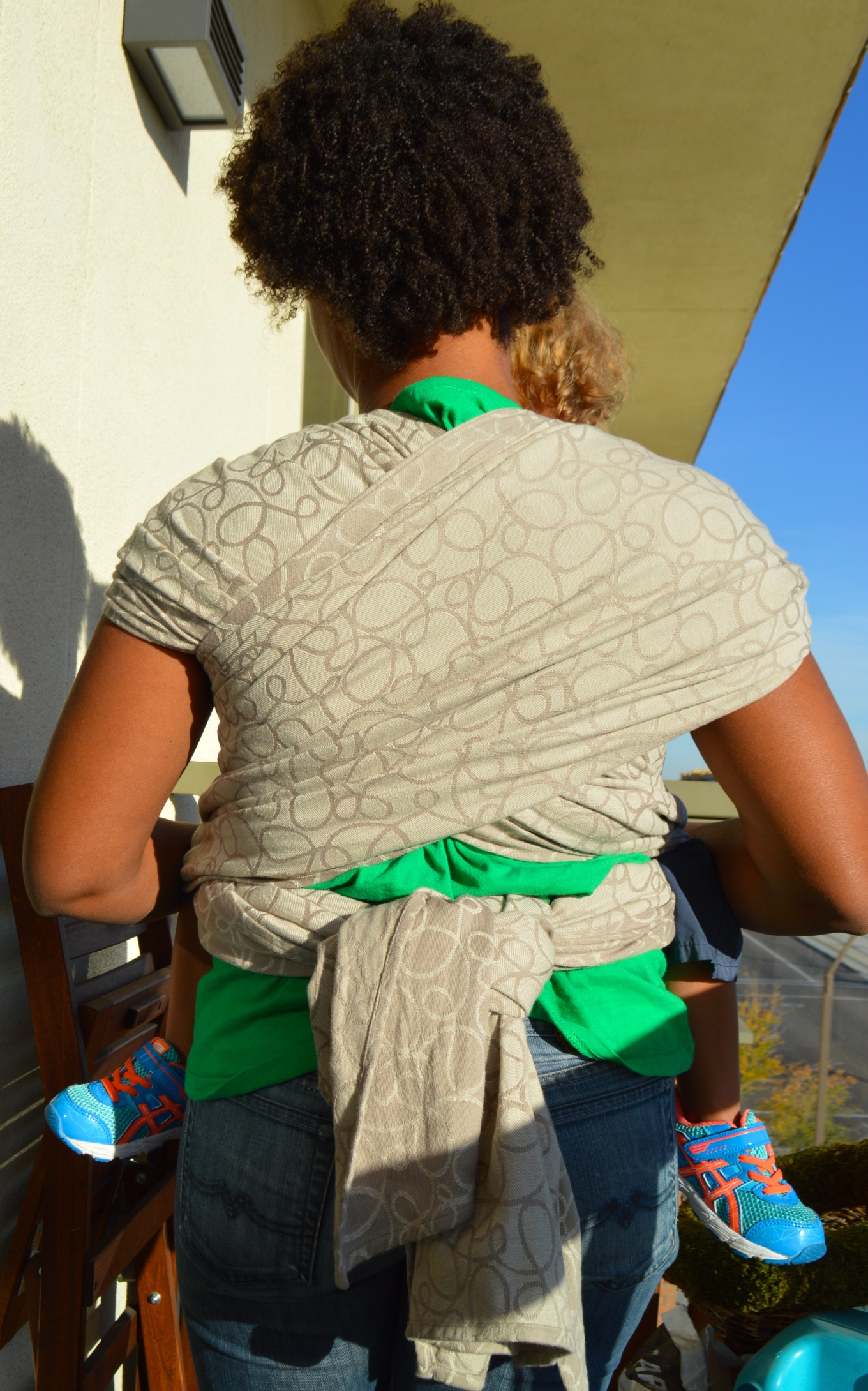 Image of the back of a medium brown Momma with dark brown natural curly hair with her light brown blond haired toddler in a front carry. The cross passes of the light tan wrap with dark tan swirls is seen with a large double knot in back.