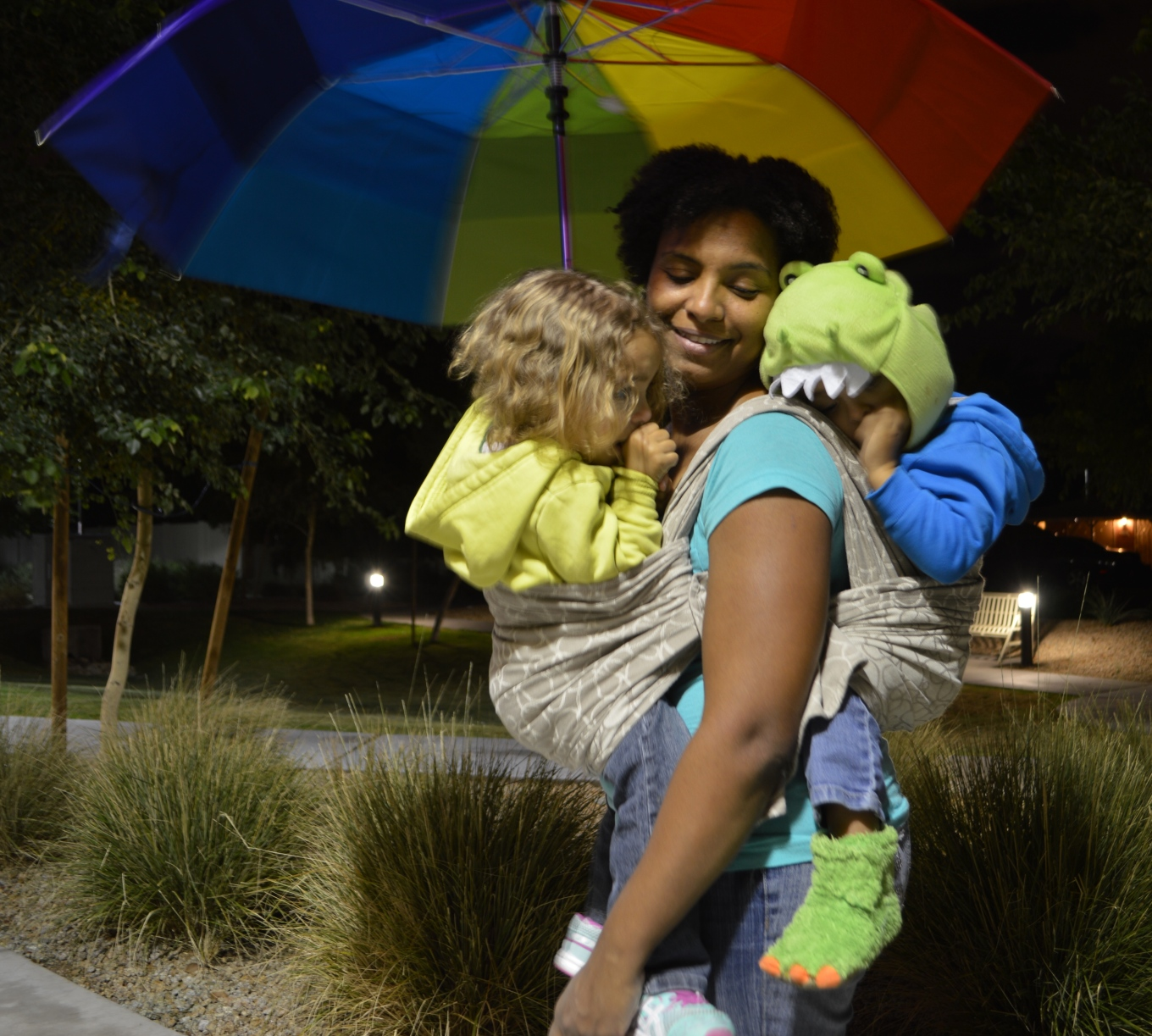 Medium brown Momma wears one toddler with dragon slippers and hat in back and light brown blond haired twin in front. Babies are in a light brown wrap with dark brown swirls. Momma is hands free to hold the large rainbow colored umbrella overhead as they walk after sunset.