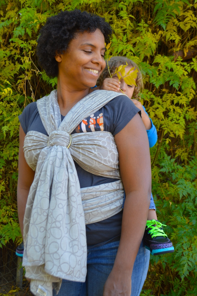 Image shows medium brown Momma with dark curly hair wearing light brown blond haired toddler in a light tan wrap with meandering swirl patterns