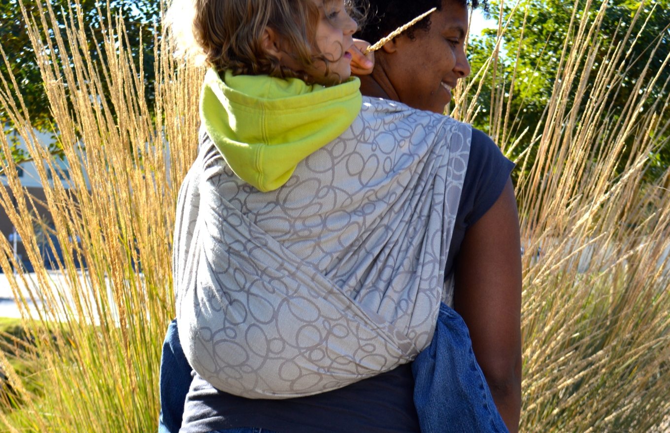 Medium brown momma with dark natural hair wears light brown blond haired toddler on her back in a light tan wrap with dark tan swirls. The carry shows the wrap crossing over baby's back in a Double Rebozo.