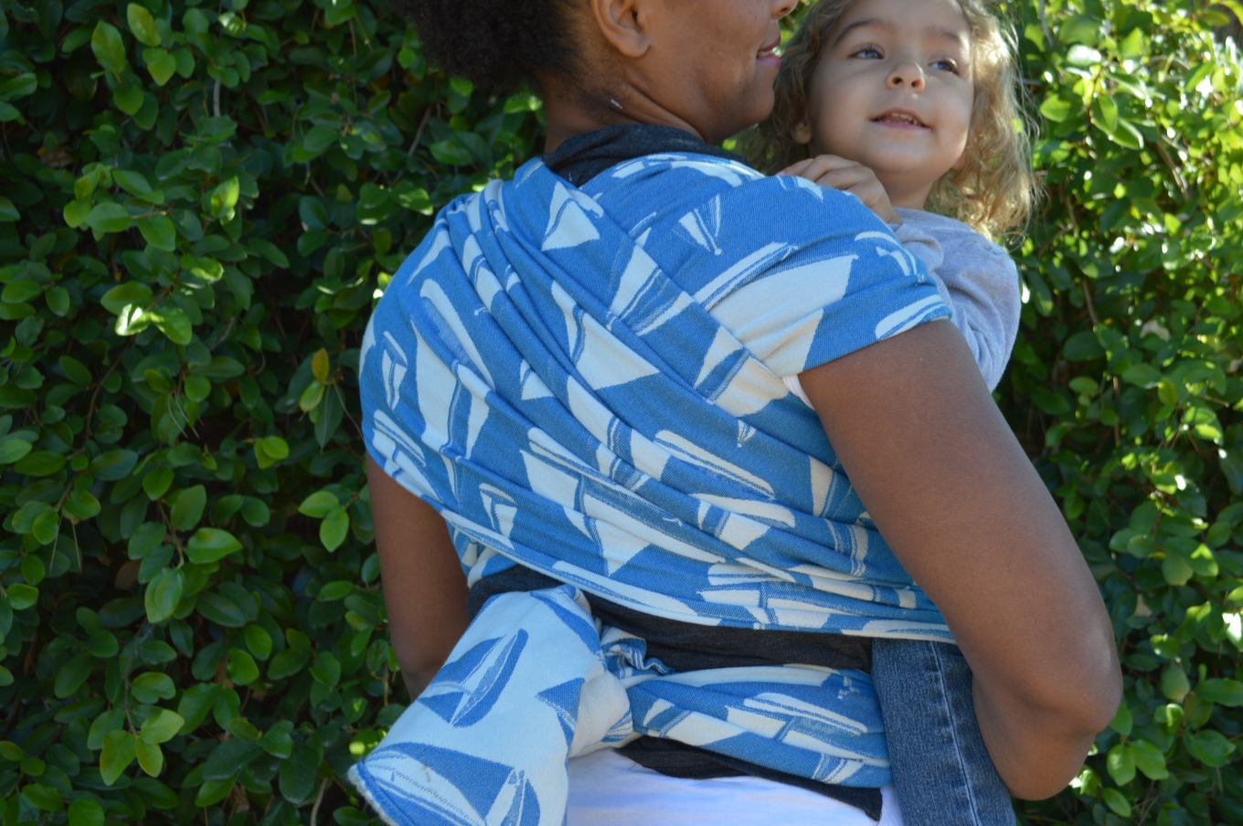 Medium brown natural haired Momma wears her baby on her back in a white and vibrant blue wrap with white sailboats.