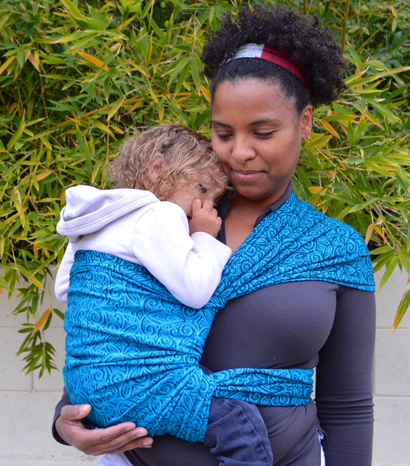 Medium brown momma with natural curly hair wears light brown blond haired toddler on her hip in a turquoise wrap with repeating small swirls pattern. The wrap is spread across the shoulder and reinforced across baby's back and bottom.
