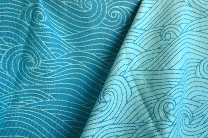 a turquoise and light blue colored wrap with repeating swirls of ocean waves.