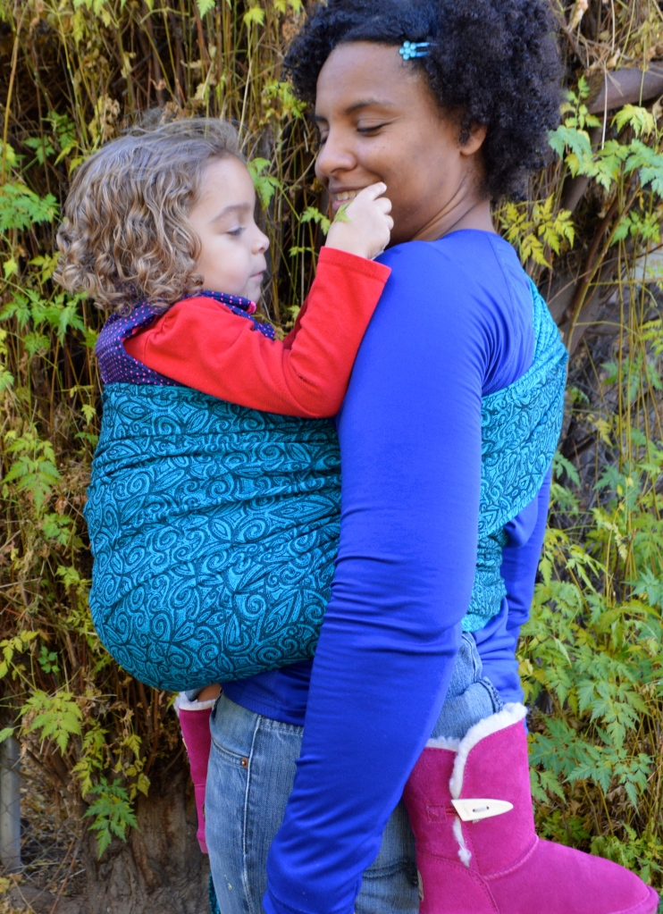 Medium brown Momma with naturally curly hair wears her light brown, blonde, curly haired toddler in front in a turquoise wrap with repeating small black swirls. Baby is playing with leaves and Momma smiles reassuringly.