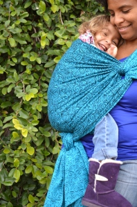 Medium brown momma with natural curly hair wears light brown blond haired toddler on her hip in a turquoise wrap with repeating small swirls pattern. The wrap is spread across the shoulder and reinforced across baby's back and bottom. Momma is out of view but baby is snuggled in with a big smile.