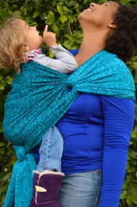 Medium brown momma with natural curly hair wears light brown blond haired toddler on her hip in a turquoise wrap with repeating small swirls pattern. The wrap is spread across the shoulder and reinforced across baby's back and bottom. Baby and Momma are looking up toward the trees.