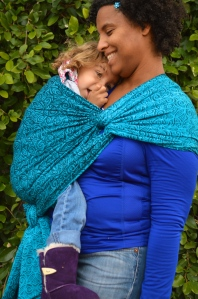 Medium brown momma with natural curly hair wears light brown blond haired toddler on her hip in a turquoise wrap with repeating small swirls pattern. The wrap is spread across the shoulder and reinforced across baby's back and bottom. Baby is snuggled in against Momma's shoulder as Momma smiles
