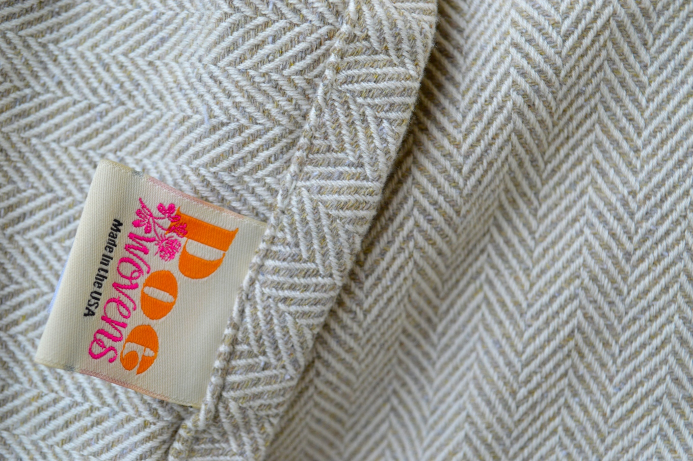 Close up Image of woven wrap with herringbone weave. The wrap is a neutral oatmeal color but comprised of colors of brown, blue, pink, and yellow against a off white to cream colored warp. The company tag reads Poe Wovens and is visible in the image.