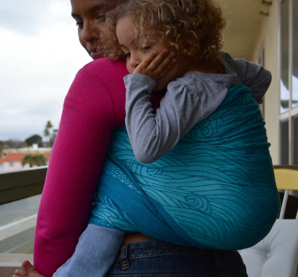 Medium brown Momma wears light brown, blonde curly haired toddler on her back in a turquoise colored wrap with repeating swirls of ocean waves.