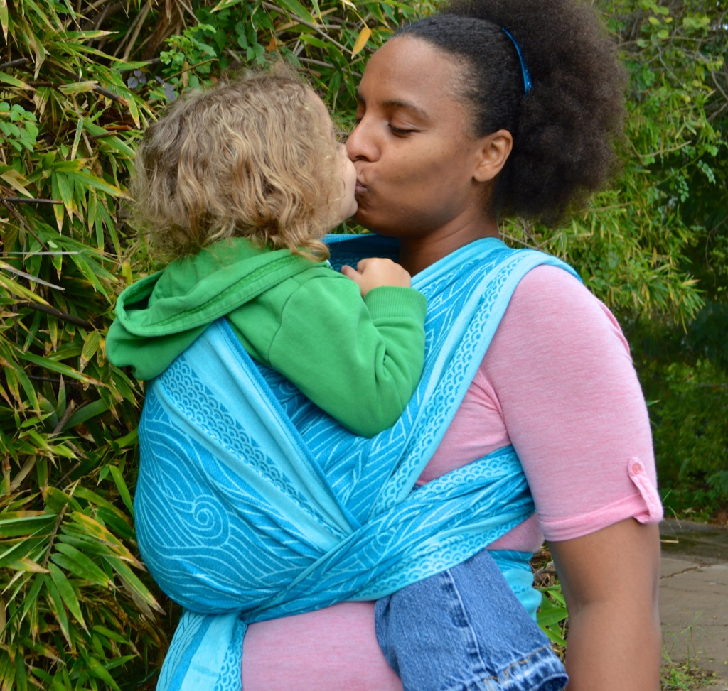 Medium brown Momma wears light brown, blonde curly haired toddler on her back in a turquoise colored wrap with repeating swirls of ocean waves. Momma and baby are kissing in the image in front of a Bamboo wall