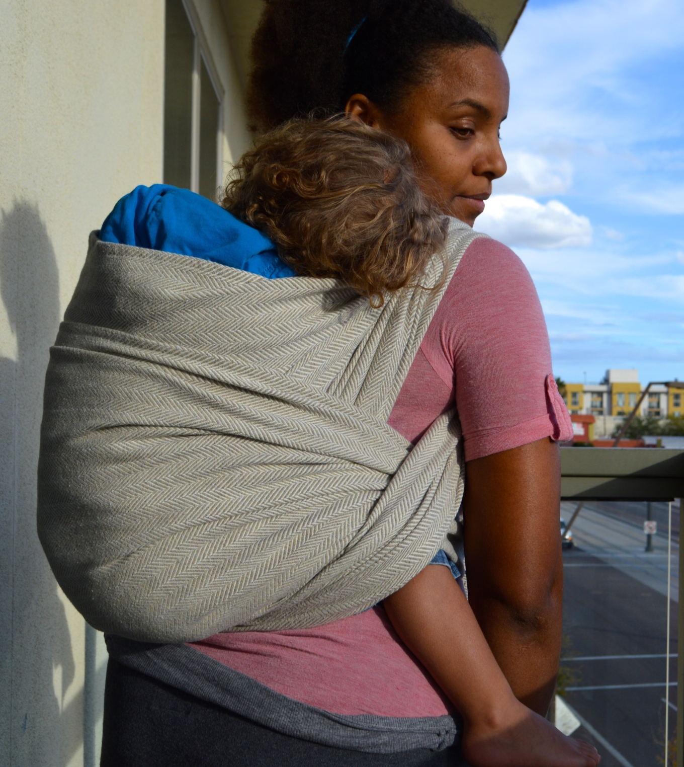Medium Brown Momma wears her light brown curly blonde haired toddler on her back in a natural oatmeal colored wrap. The wrap passes over baby's back twice and over both legs.