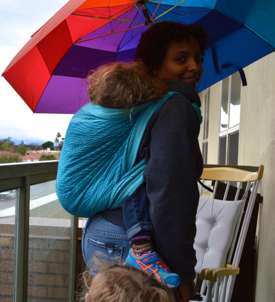 Medium brown Momma wears light brown, blonde curly haired toddler on her back in a turquoise colored wrap with repeating swirls of ocean waves. Momma is standing under a rainbow colored umbrella and baby is sleeping.