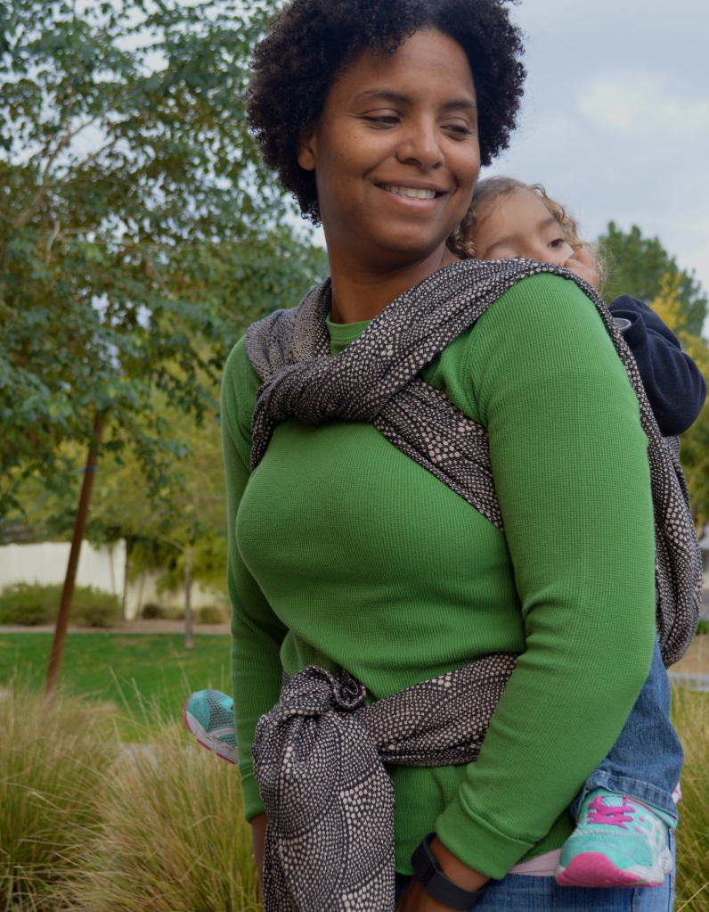 Medium Brown Momma with natural curly hair wears light brown blond, curly haired toddler on her back in a tan and black pointalism scallop designed wrap. The wrap is tied at a half knot in front at the neck and over baby's back before being tied at the waist.
