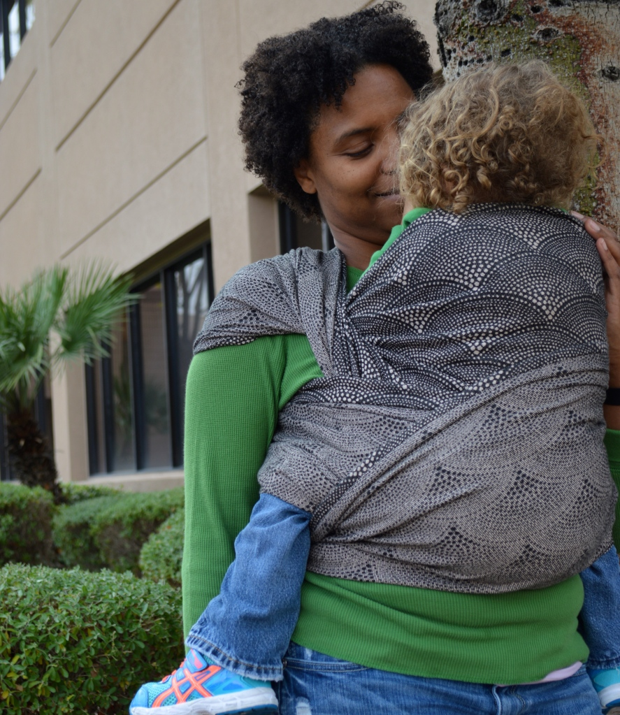 Medium Brown Momma with natural curly hair wears light brown blond, curly haired toddler on her back in a tan and black pointalism scallop designed wrap. Momma leans in for a kiss from baby. The wrap passes over baby's back and is seen twisted at the shoulder showing the other side of the wrap as the reinforced passes over baby's bum are also showing the other side of the wrap.