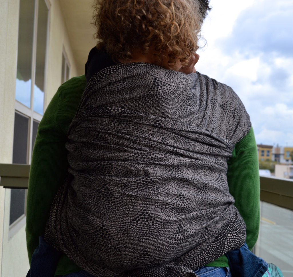 Medium brown dark curly haired Momma wears blond curly haired toddler in black and tan wrap with pointalism style scallop design. The wrap is seen from the back of the carry extending up to baby's shoulders and a secondary pass across her back.