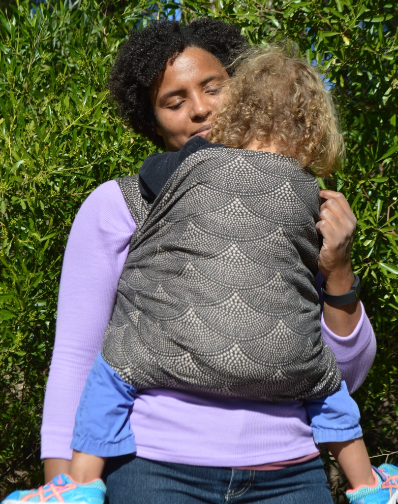 Medium brown Momma with natural dark afro curls snuggles ner light brown blond haired toddeler in a tan and black dot scallop printed wrap. The wrap is seen over Momma's shoulders and spread across baby's back to the shoulders.