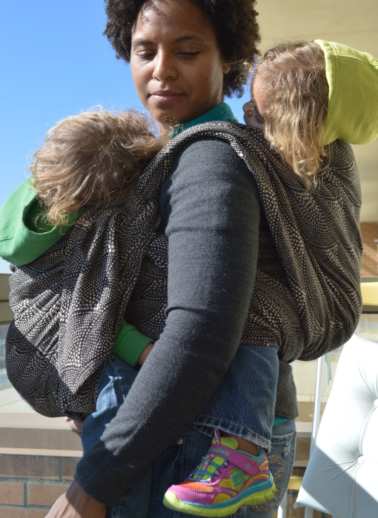 Medium Brown Momma with big afro curls wears two sleeping light brown blond haired toddlers in a wrap. One baby is in back and the other baby is in front, both resting their heads on Momma's shoulder. The wrap passes over back baby twice, tied at the shoulder then once over front baby's back tied on the opposite shoulder strap.