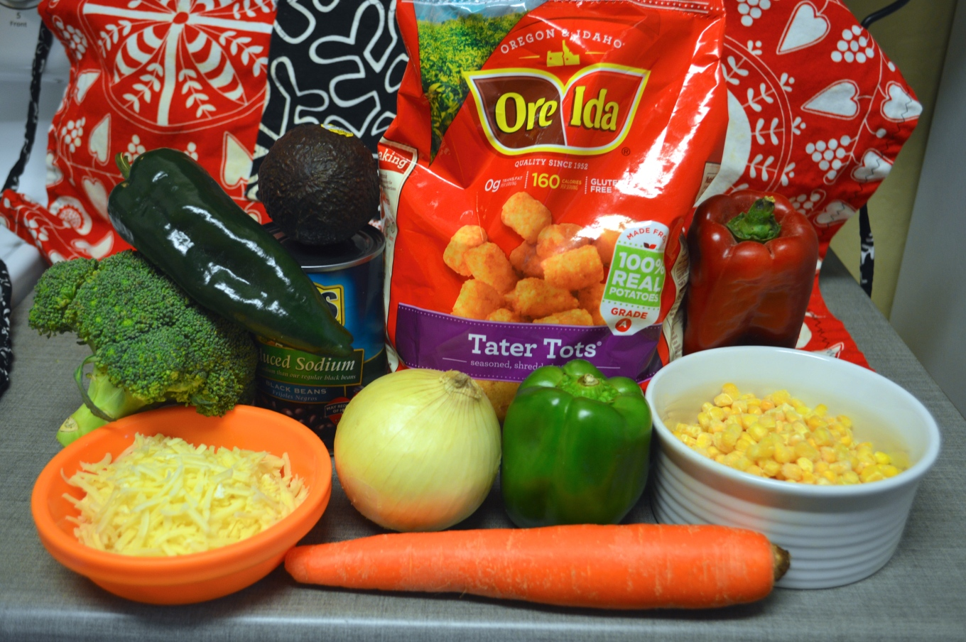 Image shows a bag of Ore-Ida frozen tots at the center with raw veggetables including broccoli crown, onion, green and red bell peppers, carrot, frozen sweet corn in a white dish, a poblano pepper, an avocado, and a can of black beans.