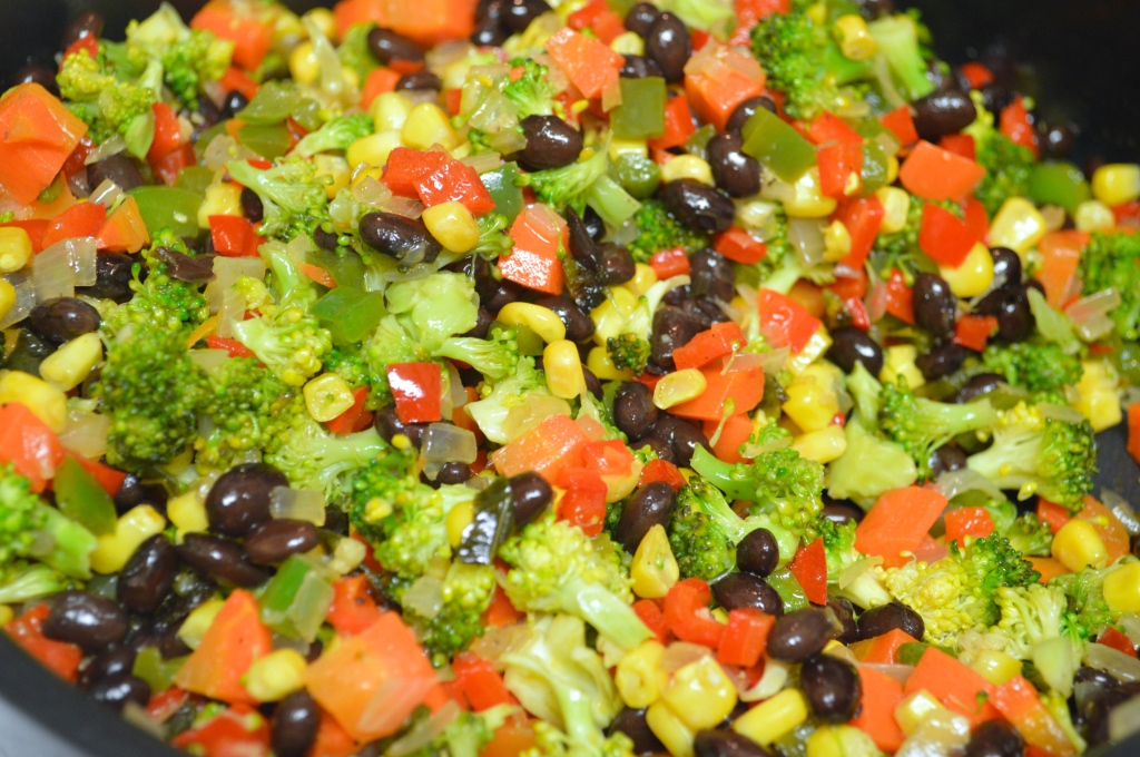 Image shows gently sauteed vegetables including carrots, broccoli, black beans, corn, red and green bell peppers, onion, and garlic
