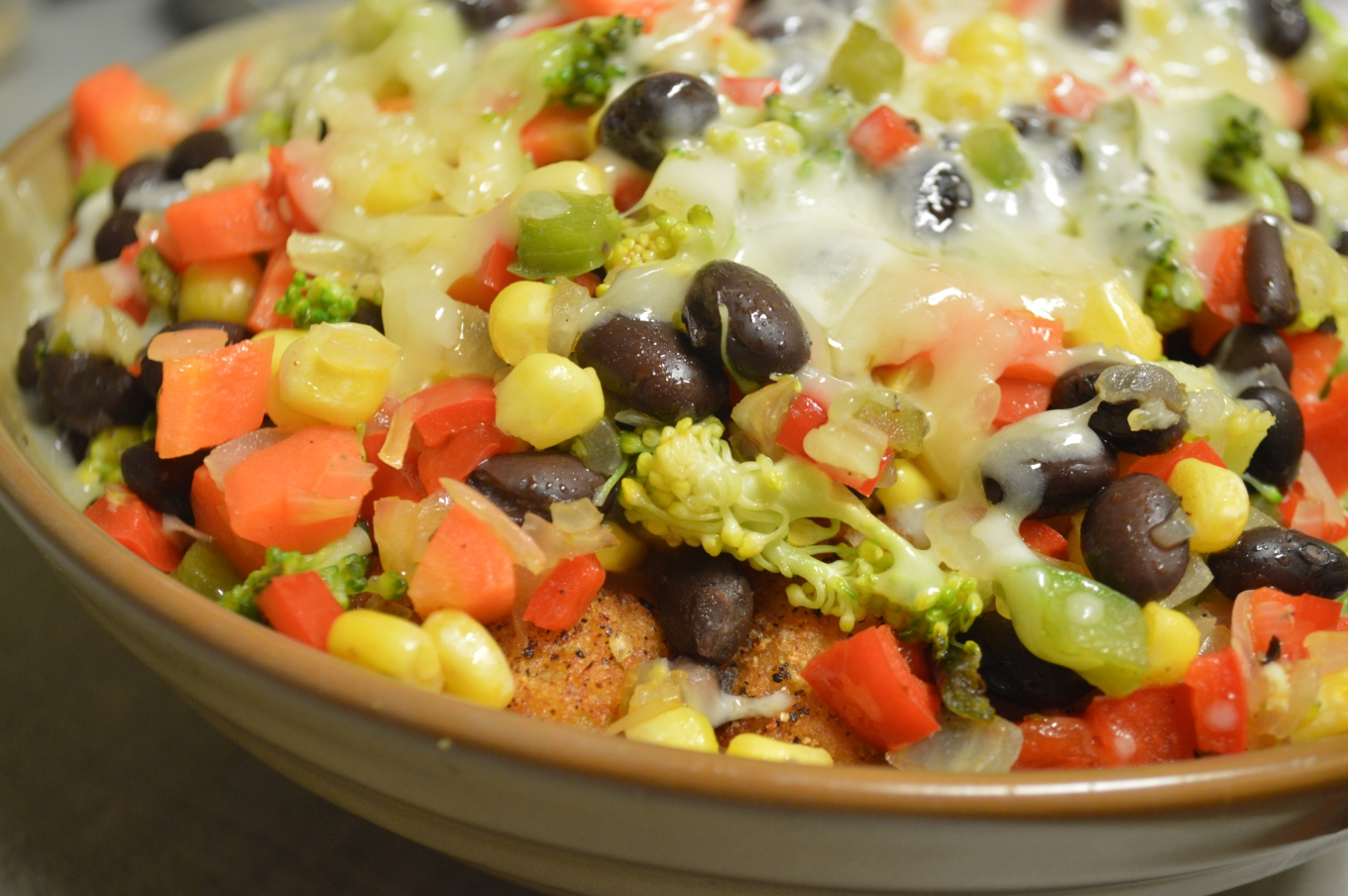 Image shows a bowl with seasoned browned tater tots, black beans, corn, sauteed red bell pepper, roasted poblano peppers, sauteed green bell peppers and onions, steamed broccoli and carrots. The vegetables are layered with the seasoned tots and cheese, melted across the top and in the center