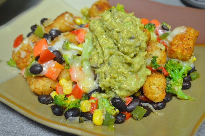 Image shows a bowl with seasoned browned tater tots, black beans, corn, sauteed red bell pepper, roasted poblano peppers, sauteed green bell peppers and onions, steamed broccoli and carrots. The vegetables are layered with the seasoned tots and cheese, melted across the top and in the center. The food is topped with guacamole.