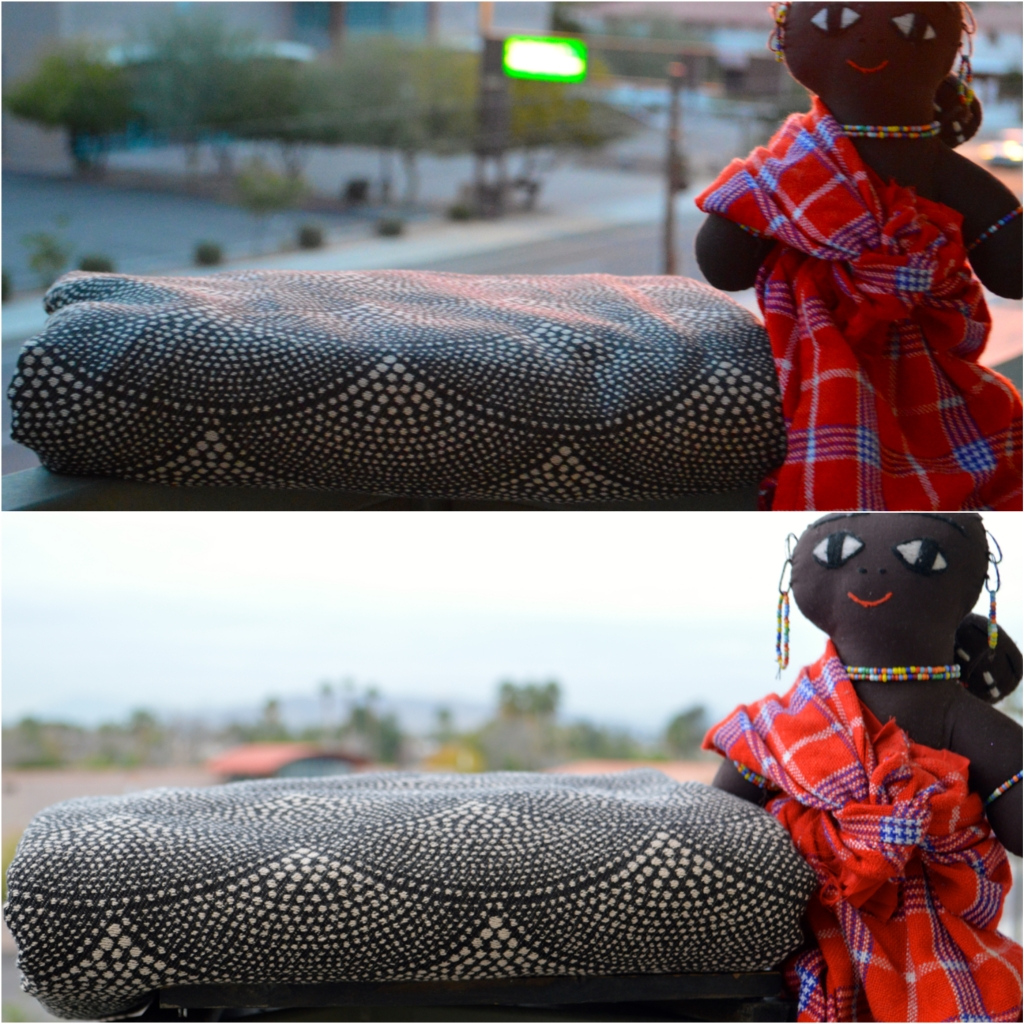 The image is a collage of two images, one on top and the other on bottom. The top image shows the loom state wrap with the dominant black with tan pointallism scallop print next to an African babywearing Maisai Mara doll. The wrap is approximately one inch below the arm of the doll at sunset. The lower image shows the wrap after washing in the same fold pattern and color pattern showing as the image above. The wrap is next to the same babywearing doll but this time is taller than the doll's arm by three inches.
