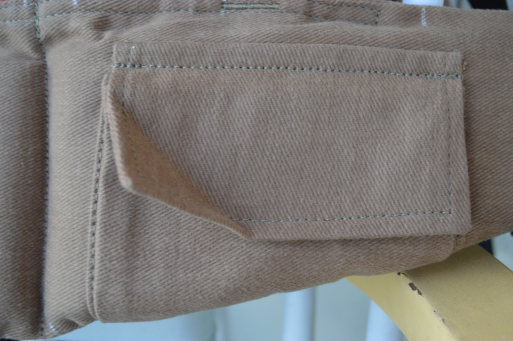 Close up view of the small credit card sized pouch on the waistband in th same soft brown khaki color of the carrier waistband.