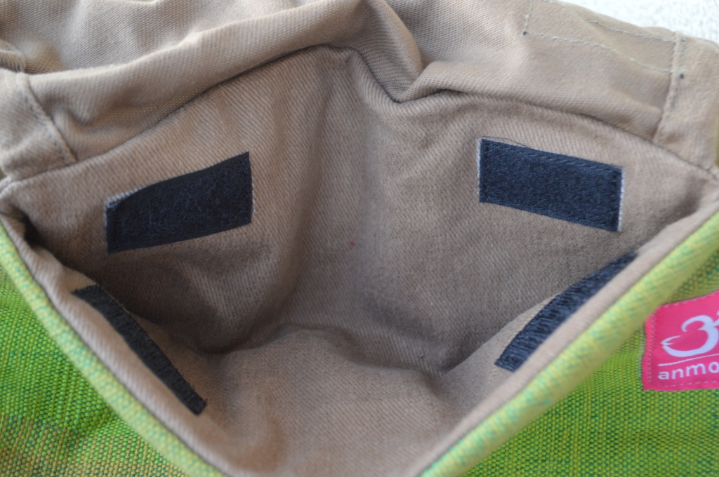 Image shows the inside of the hood stowaway pouch at the top of the carrier body. The khaki inside is soft brown and the four velcro strips to keep the hood pouch closed can be seen in the image